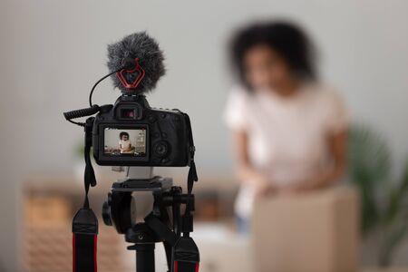Vlogger utilisant un appareil photo numérique professionnel avec microphone en gros plan, enregistrement d'une vidéo de déballage de colis pour la chaîne sur le réseau social, examen des produits, boîte en carton avec commande en ligne
