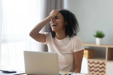 Overjoyed African American woman businesswoman excited by successful business solution, happy student freelancer laughing loud at funny joke and touching forehead at workplace, having fun