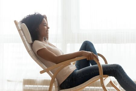 Smiling African American woman resting in rocking chair close up, satisfied girl resting in cozy chair at home, spending lazy day weekend, daydreaming, enjoying free time, dreaming about future