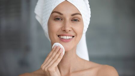 Smiling beautiful young woman with towel on head hold cotton pad disk cleansing face skin with cleanser, happy lady remove makeup look at camera enjoy healthy clean skincare beauty treatment concept