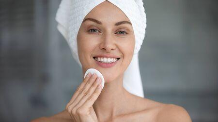 Sonriente a mujer joven hermosa con una toalla en la cabeza sostenga el disco de la almohadilla de algodón que limpia la piel de la cara con el limpiador, la señora feliz quita el maquillaje mira a la cámara y disfruta del concepto de tratamiento de belleza de cuidado de la piel limpio saludable Foto de archivo