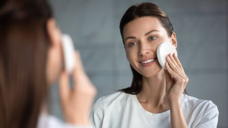 Healthy smiling beautiful young lady cleaning purifying facial skin care holding cleansing exfoliating sponge, happy woman remove makeup with cleanser looking in mirror, skincare treatment concept Imagens