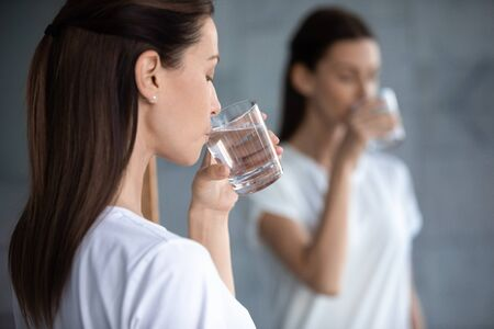 Thirsty young woman hold glass drink fresh clean water reflecting in mirror, dehydrated healthy lady hydrate thirst in morning keep healthcare balance for skin body care concept, over shoulder view