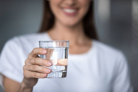 Smiling young lady holding fresh transparent pure filtered mineral water, happy healthy adult woman offering glass to camera as health care thirst hydration natural nutrition concept, close up view Imagens