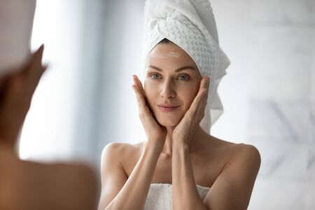 Beautiful young woman look in mirror massaging face applying cream in bathroom, pretty lady wrap towel on head put facial moisturizer lifting hydrating moisturizing creme, skin care treatment concept