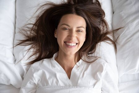 Happy beautiful young woman awake after healthy sleep lying in cozy comfortable white bed on pillow, smiling lady waking up enjoy good morning feel fresh looking at camera, close up portrait top view Imagens