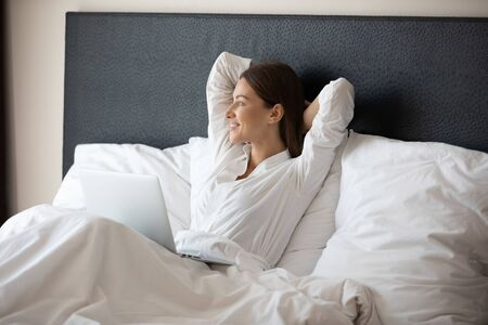 Happy fresh relaxed young woman resting sitting in bed wear pajamas using laptop enjoying good morning after wakeup at modern home hotel bedroom looking outside relaxing alone with device concept
