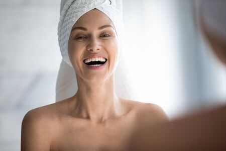 Happy young woman with towel on head laughing looking in mirror camera, cheerful attractive happy lady with white teeth dental smile healthy skin having fun do morning routine in bathroom, portrait