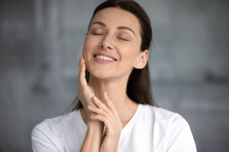 Smiling attractive young woman touching hydrated moisturized healthy facial skin, happy lady enjoy beauty rejuvenation face skincare moisture spa treatment hydration concept standing in bathroom
