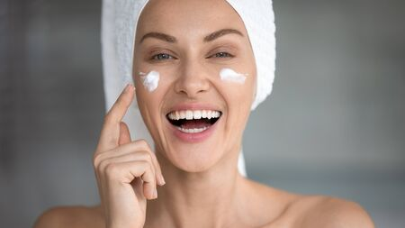 Cheerful attractive young woman apply facial creme laughing looking at camera, happy lady wrap towel on head putting cream lifting hydrating moisturizing on face skin care concept, close up portrait
