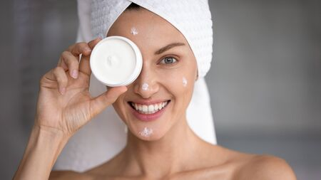 Happy attractive young woman hold creme jar cover eye look at camera, smiling lady wrap towel on head apply cream on face in bathroom, facial skin care treatment, skincare concept, close up portrait