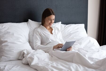 Happy young woman in nightwear holding digital pad tablet computer sitting in bed in morning, smiling lady using apps reading electronic book relax in bedroom enjoy browsing social media at home