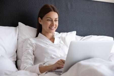 Smiling young beautiful woman using laptop apps wear pyjamas sitting in cozy bed in morning browsing internet surfing social media holding typing on computer device after waking up in modern bedroom