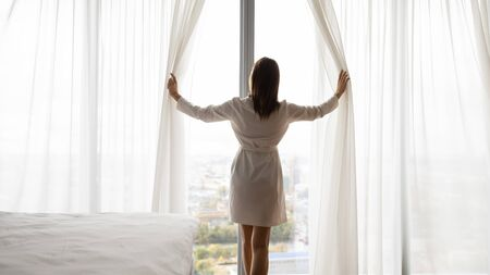 Happy rich young woman wear night robe stand at big window open lace curtains in bedroom look outside enjoy view dream feel motivated in modern home hotel, good morning lifestyle concept, rear view Stockfoto