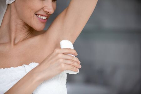 Smiling young woman wrapped in white towel hold applying antiperspirant in armpit, happy lady use deodorant stick in underarm, daily hygiene hyperhidrosis treatment protection concept, close up view Imagens