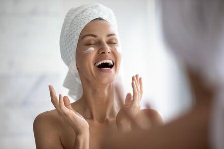 Positive lustige junge Frau lacht beim Auftragen von Gesichtscreme, die sich im Spiegel spiegelt, glückliche attraktive Dame legte feuchtigkeitsspendende, pflegende Creme auf, die Morgenroutine im Badezimmer macht, Hautpflegekonzept