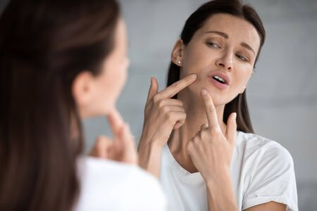 Frustrated young adult woman looking in mirror feeling stressed upset about facial skin problem concept wrinkles or pimple, worried depressed lady touch face annoyed by blackhead acne in bathroom