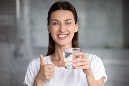 Happy healthy young attractive woman holding glass of fresh mineral pure clean filtered water showing thumbs up look at camera recommend hydration balance for skin body healthcare concept, portrait