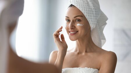 Smiling pretty lady put anti-ageing hydrating moisturizing lifting nourishing facial cream in bathroom, happy young woman wrap in towel look in mirror apply creme on face skin care treatment concept