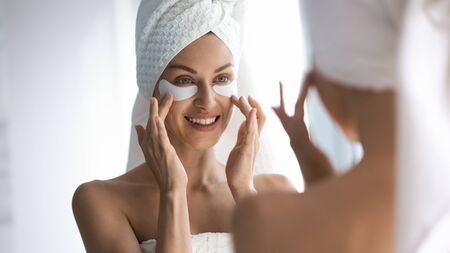 Happy young woman with towel on head apply eye care patches on face looking in mirror, 30s beautiful lady using under eye skin care dark circles and bags spa treatment concept standing in bathroom