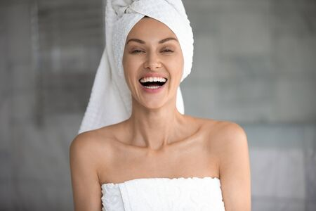 Positive young lady wrapped in towels laughing looking at camera, happy beautiful 30s woman with white teeth dental smile healthy face skin posing in bathroom after sauna morning routine, portrait