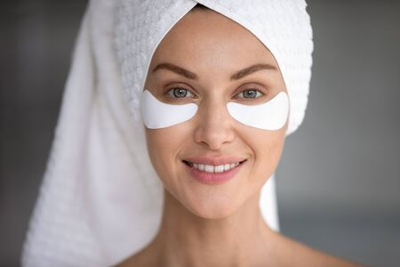 Smiling healthy young lady wrap towel on head look at camera with eye care patches on face, happy pretty woman using undereye skin beauty dark circles bags treatment concept, close up view portrait