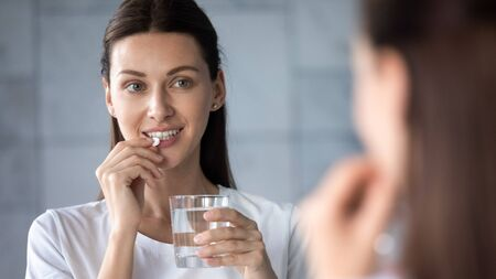 Young healthy woman holding pill glass of water looking in mirror, adult lady take daily medicine diet vitamin omega supplements for beauty skin hair health care medicament stand in bathroom concept