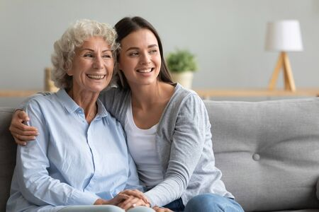 Caring young adult daughter granddaughter hug elderly old grandmother mother bonding looking away sit on sofa, happy two generation women family think dream of good future give help support concept