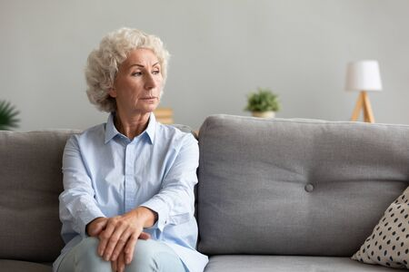 Thoughtful pensive senior grandma looking away thinking of loneliness sit on couch, melancholic worried serious old elderly woman lost in thought about depression wait support alone on sofa at home