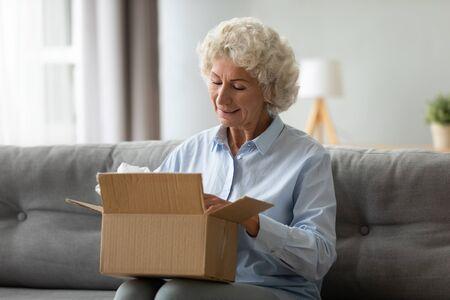 Il cliente anziana sorridente riceve il pacco postale della spedizione a casa, la nonna anziana felice tiene aperta la scatola di cartone seduta sul divano in soggiorno, lo shopping online ordina il concetto di consegna veloce del corriere