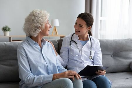 Caring young woman nurse help old granny during homecare medical visit, female caretaker doctor talk with elder lady give empathy support encourage patient sit on sofa older people healthcare concept