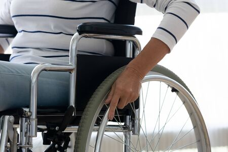 Handicapped senior woman hold hand push wheel sit on wheelchair, disabled paralyzed old grandma moving using disability equipment, invalid patient healthcare rehabilitation concept, close up view