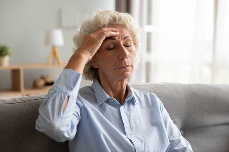 Boos senior oudere dame die voorhoofd aanraakt duizelig onwel hoofdpijn pijn concept, verdrietig moe oude volwassen oma die lijdt aan hypertensie, migraine, mentaal probleem of vermoeidheid zit thuis op de bank Stockfoto