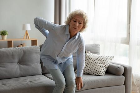 Stressed old senior adult lady touching back feel lower lumbar ache getting up from sofa at home, upset elderly grandma suffer from backache health problem, osteoarthritis disease, backpain concept Zdjęcie Seryjne