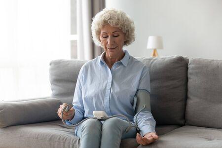 Ältere ältere Frau misst hohen niedrigen Blutdruck, der mit einem medizinischen digitalen elektronischen Messgerät auf dem Sofa zu Hause sitzt, Herzkrankheit-Arteriosklerose-Prävention, Hypotonie-Hypertonie-Konzept