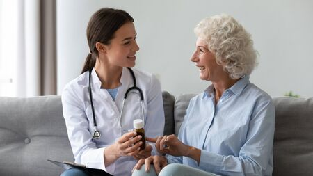Smiling woman doctor prescribing medicine giving vitamins bottle to happy senior grandmother patient sit on sofa during medical healthcare visit, older people pharmacy medication treatment concept