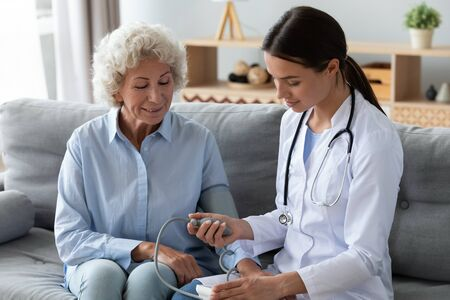 Young female nurse doctor measure high low blood pressure check old woman grandma hypertension sufferer using medical digital electronic tonometer at home, senior people cardiology healthcare concept
