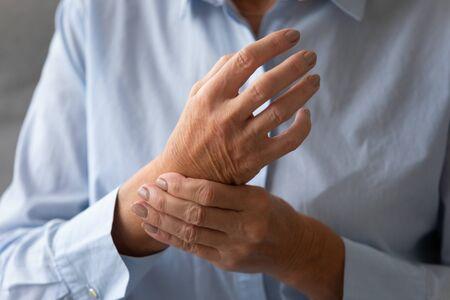 Signora anziana che massaggia la mano che soffre di concetto di artrite reumatoide, paziente anziana adulta che tocca il polso sentendosi ferita dolore articolare con problemi di salute della malattia dell'osteoartrite, vista ravvicinata