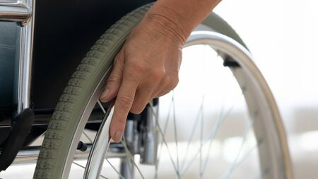 Senior disabled person hand holding pushing wheel close up view, handicapped paralyzed elderly adult grandmother invalid patient moving sitting on wheelchair, disability equipment mobility concept