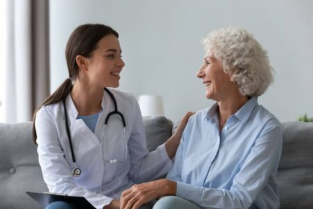 Happy young female nurse provide care medical service help support smiling old grandma at homecare medical visit, lady carer doctor give empathy encourage retired patient sit on sofa at home hospital