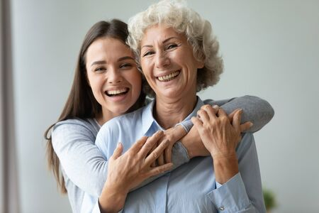 Cheerful affectionate two age generation women embracing indoor, happy young adult daughter granddaughter hug old retired grandmother mom laughing bonding looking at camera at home, family portrait
