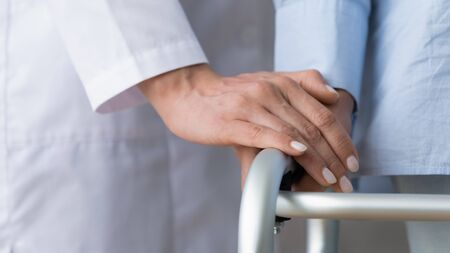 Female doctor nurse carer hold elder patient hand use walking frame, woman carer help assist disabled injured old granny stand with walker in hospital home, senior physiotherapy concept close up view
