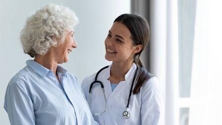 Lächelnde, fürsorgliche junge Krankenschwester, Ärztin, Hausmeisterin, die glückliche ältere Oma unterstützt, die alten Patienten bei der Rehabilitation bei einem medizinischen Check-up-Besuch hilft, Konzept für die häusliche Pflege älterer Menschen