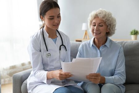Smiling older woman patient and young nurse doctor holding papers reading health life insurance medical service contract agreement look at test results during homecare visit at home hospital concept