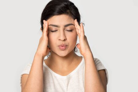 Stressed Indian girl massaging temples close up isolated on grey studio background, unhappy young woman with closed eyes suffering from headache, feeling pain, tension, migraine, health problem