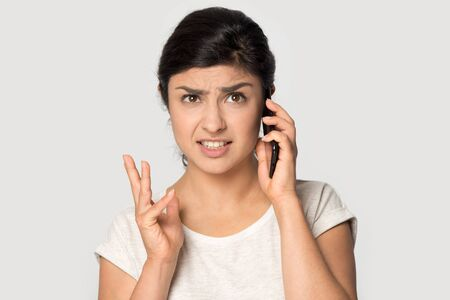 Annoyed furious Indian girl talking on phone isolated on grey studio background close up, argument, angry young woman irritated by bad news or spam, problem with cellphone call, unpleasant message Stock fotó