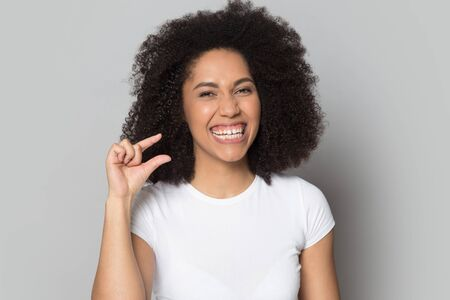 Head shot smiling African American girl showing little size gesture, laughing, having fun, isolated on grey studio background, young female looking at camera, small prices, shopping sales discount
