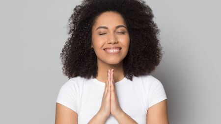 Head shot grateful smiling African American girl with closed eyes folded hands in prayer, pleased young female feeling love, thanking fate, making wish, standing isolated on grey background Stock Photo