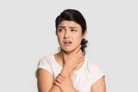 Sick upset Indian girl touching neck, suffering from sore throat, standing isolated on grey studio background, unhappy young woman feeling bad, unwell, painful swallowing, illness concept