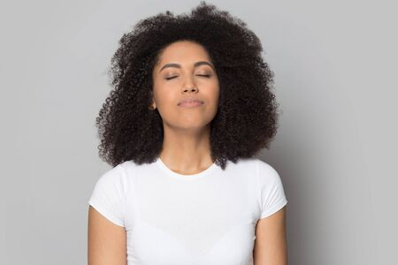Head shot close up relaxed African American girl with closed eyes breathing deep, meditating, dreaming about future, isolated on grey studio background, mindful female enjoying break, pause